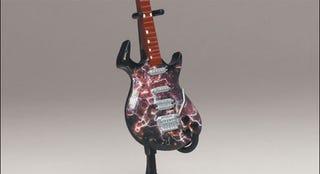 Illustration for article titled McFarlane's Tiny, Plastic Guitar Hero Guitars