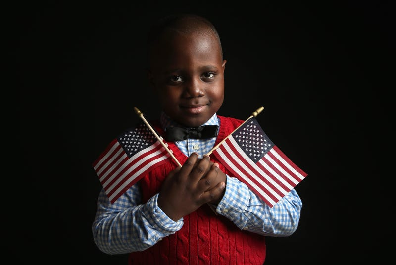 Ifeozuwa Oyaniyi, 5, born in Nigeria, holds flags given to him by the U.S. Citizenship and Immigration Services while waiting to receive his citizenship certificate on Feb. 19, 2013, in New York City. (John Moore/Getty Images)