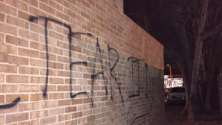 "Shortly after video surfaced purportedly showing members of a chapter of Sigma Alpha Epsilon singing a racist chant, someone spray-painted ""Tear It Down"" on the side of the frat house at the University of Oklahoma. (NBC News screenshot)"