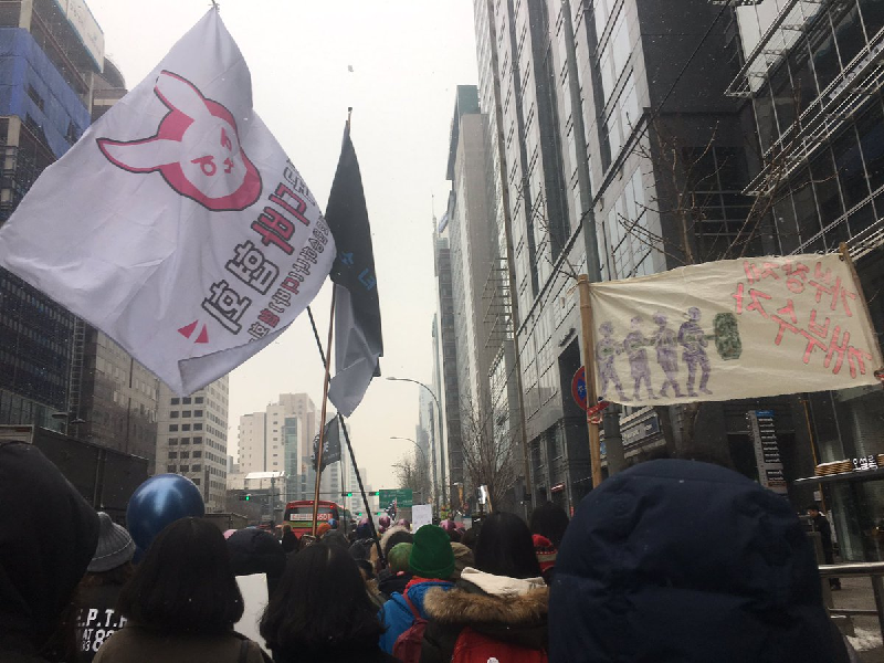 Women marching earlier today in Seoul with a flag or D.Va's bunny symbol, via @marchseoul.