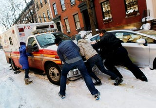 Residents try to help first responders move their vehicle.
