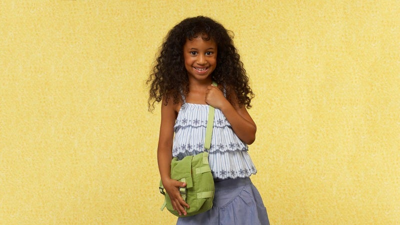 A young girl using a purse.