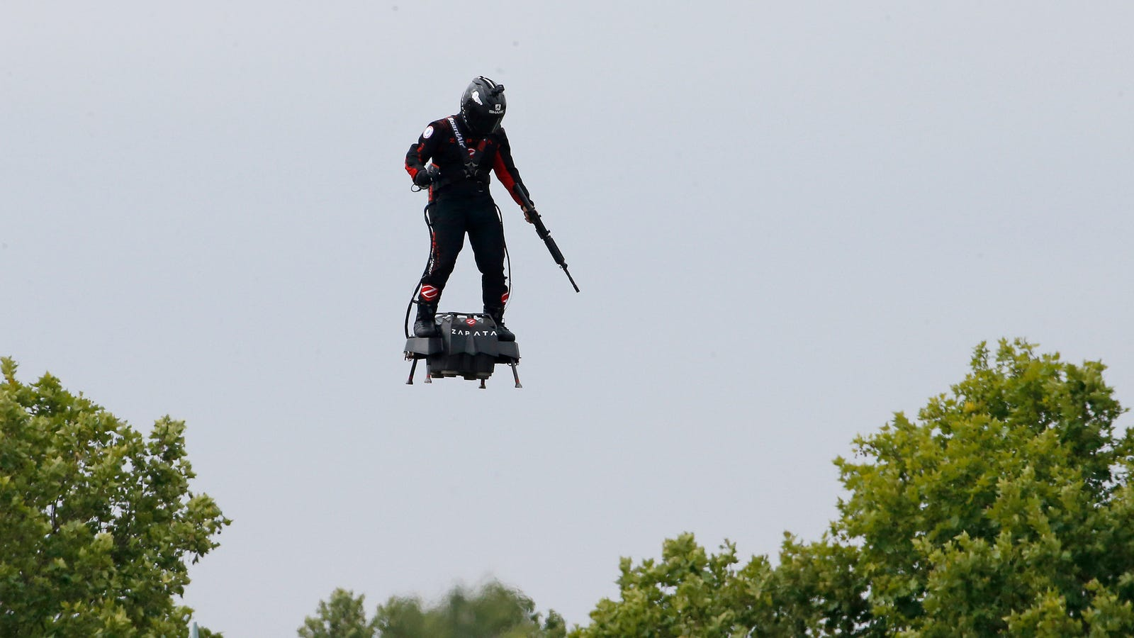 French Inventor Touts Rifle While Flying Turbine-Powered Flyboard at Bastille Day Celebrations