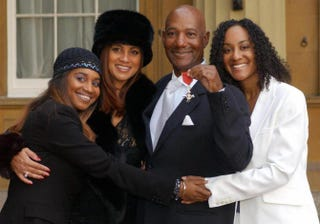 Errol Brown with his wife, Ginette (second from left), and daughters, Leonie (left) and Colette, after receiving an MBE for services to pop music from Queen Elizabeth II at Buckingham Palace in London Nov. 27, 2003FIONA HANSON/AFP/Getty Images