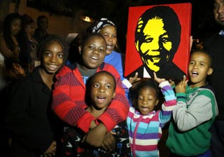 South Africans pay tribute to South African President Nelson Mandela following his death in Johannesburg on Dec. 6, 2013.ALEXANDER JOE/AFP/Getty Images