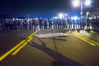Police in Ferguson, Mo., stand guard as demonstrators, marking the one-year anniversary of the fatal police shooting of Michael Brown, protest Aug. 10, 2015.Scott Olson/Getty Images