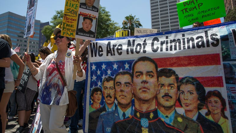 A banner references immigrants who serve in the U.S. military but face possible deportation during the Impeachment March on July 2, 2017 in Los Angeles, California. Image via Getty.