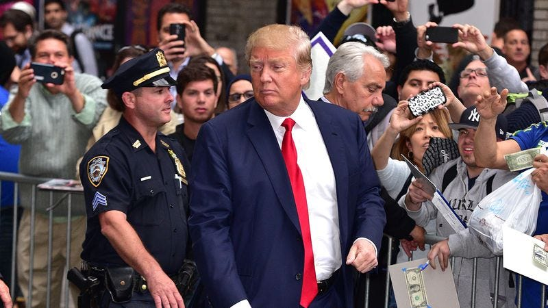 Donald Trump, probably being escorted to jail for crimes against spray-on bronzer (Credit: Getty Images)