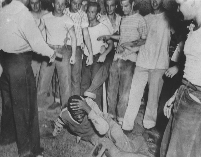A mob of white teenagers kick and beat an African-American man, who holds his head and screams in pain during a lynching, 1950.Afro American Newspapers/Gado/Getty Images