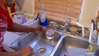 A resident of Flint, Mich., runs water from her faucet.Al-Jazeera America screenshot