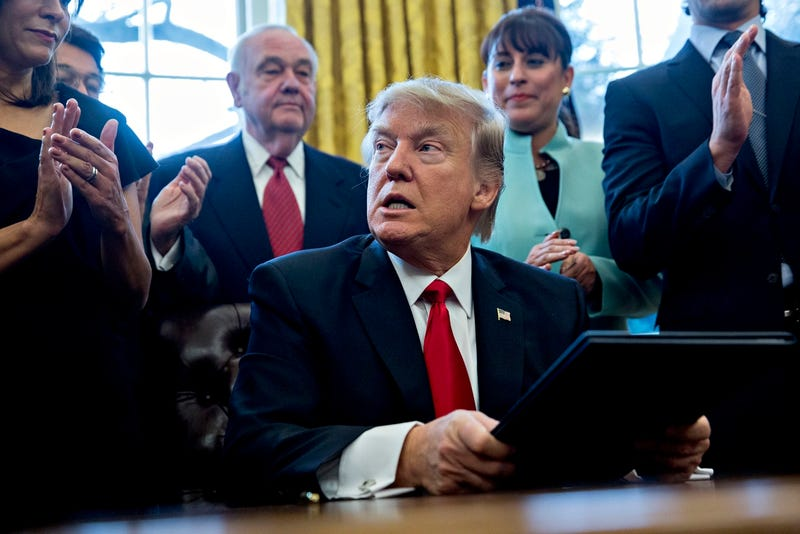 President Donald Trump signs executive orders in the Oval Office on Monday, January 30, 2016 while sycophants applaud (Photo by Andrew Harrer - Pool/Getty Images)