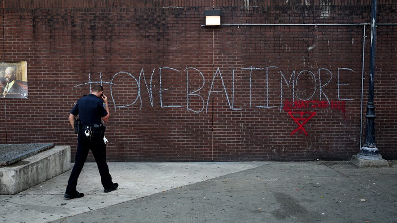 "A police officer walks by a tagging reading ""One Baltimore"" on the corner of North and Pennsylvania Avenues in Baltimore on May 2, 2015, a day after authorities released a report on the death of Freddie Gray. (Patrick Smith/Getty Images)"