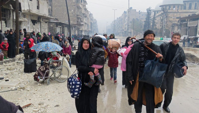 Syrian residents flee to the Fardos neighborhood of Aleppo, which was recently retaken by a regime that is said to be summarily executing civilians. Image via STRINGER/AFP/Getty Images.