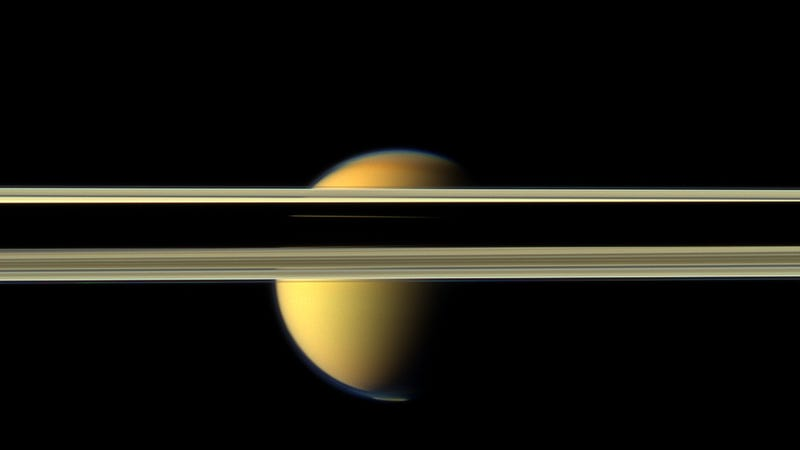 Titan, partially obscured by Saturn's rings. Image: NASA/JPL-Caltech/Space Science Institute