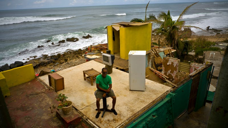 Roberto Figueroa Caballero sitting on a small table in his home that was destroyed by Hurricane Maria on the coast of San Juan, Puerto Rico. Photo: AP