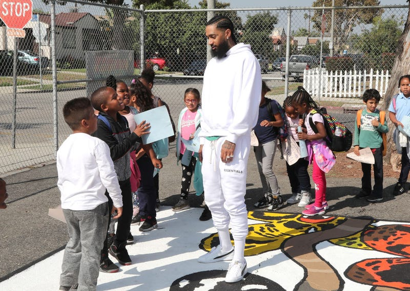 Nipsey Hussle greets kids at the Nipsey Hussle x PUMA Hoops Basketball Court Refurbishment Reveal Event on Oct. 22, 2018, in Los Angeles.