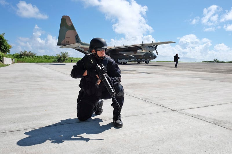 A Taiwanese soldier secures the perimeter of an C-130 transport plane during a search-and-rescue exercise off Taiping island, in the South China Sea , Tuesday, Nov. 29, 2016, as part of efforts to cement its claim to a key island in the strategically vital waterbody. (AP Photo/Johnson Lai)