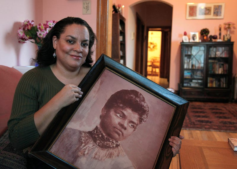 In this Dec. 2, 2011, photo, Michelle Duster, great-granddaughter of journalist and civil rights pioneer Ida B. Wells, holds a portrait of Wells in her home in Chicago's South Side.