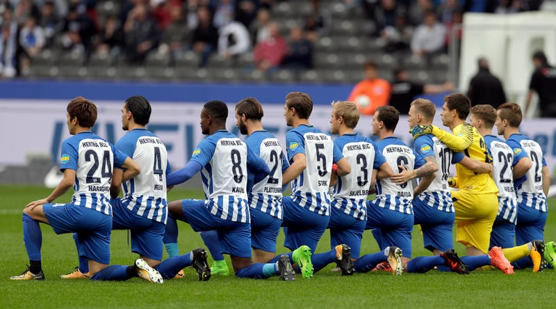 Players of Berlin kneel prior to the German Bundesliga soccer match between Hertha BSC Berlin and FC Schalke 04 in Berlin on Oct 14, 2017. (Michael Sohn/AP Images)