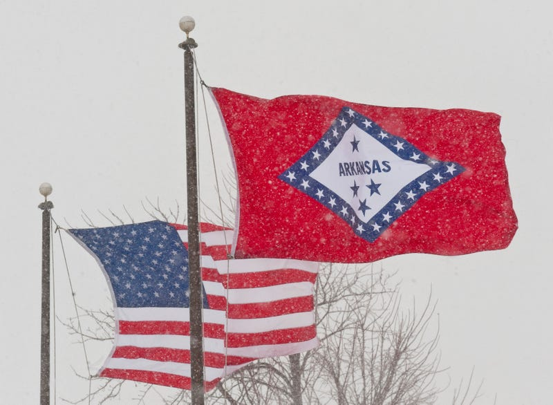 In a February 2011 file photo, the U.S. and Arkansas flags blow in the wind in Fayetteville, Ark. Arkansas has decided to remove two Confederate-era statues representing it in Statuary Hall, but the state still has refused to change the meaning of a star on the state's flag that currently represents the Confederacy.