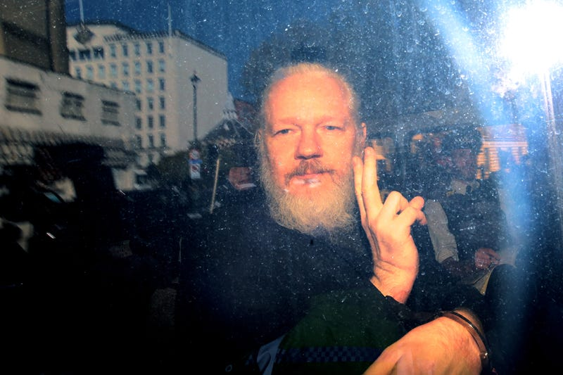 Julian Assange gestures to the media from a police vehicle on his arrival at Westminster Magistrates court on April 11, 2019 in London, England. After weeks of speculation, Wikileaks founder Julian Assange was arrested by Scotland Yard Police Officers inside the Ecuadorian Embassy in Central London this morning. Ecuador's President, Lenin Moreno, withdrew Assange's Asylum after seven years citing repeated violations to international conventions.