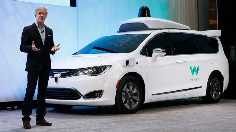 Waymo's CEO John Krafcik standing before a Chrysler Pacifica self-driving test car. Photo Credit: AP
