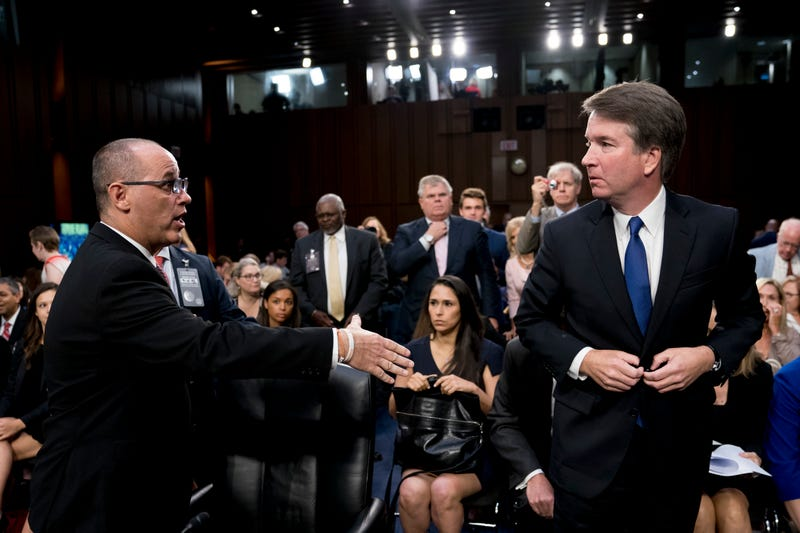 Fred Guttenberg, the father of Jamie Guttenberg who was killed in the Stoneman Douglas High School shooting in Parkland, Fla., left, attempts to shake hands with President Donald Trump's Supreme Court nominee, Brett Kavanaugh, right, as he leaves for a lunch break while appearing before the Senate Judiciary Committee on Capitol Hill in Washington, Tuesday, Sept. 4, 2018, to begin his confirmation to replace retired Justice Anthony Kennedy. Kavanaugh did not shake his hand.