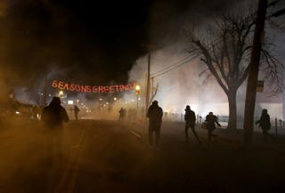 Protesters run away after police deploy tear gas during a demonstration Nov. 24, 2014, in Ferguson, Mo.Justin Sullivan/Getty Images
