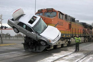Illustration for article titled Train Skewers Car Carrier In Washington, Gets Cadillac DTS Hood Ornament