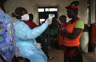 A Liberian Ministry of Health worker checks people for Ebola symptoms at a checkpoint near the international airport on Aug. 24, 2014, near Dolo Town, Liberia.John Moore/Getty Images