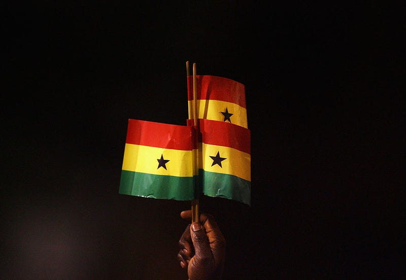 A Ghana fan holds up Ghanaian flags during an international soccer game. Ryan Pierse/Getty Images