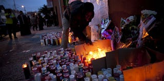 A man lights a candle at a memorial for Kimani Gray in Brooklyn, N.Y. (Allison Joyce/Getty Images)