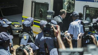 Oscar Pistorius (wearing suit), the double-amputee Olympic athlete, walks into a police van Oct. 21, 2014, under police escort in Pretoria, South Africa, after being sentenced in court there to five years in prison for killing his girlfriend, Reeva Steenkamp, on Valentine's Day 2013. MUJAHID SAFODIEN/AFP/Getty Images
