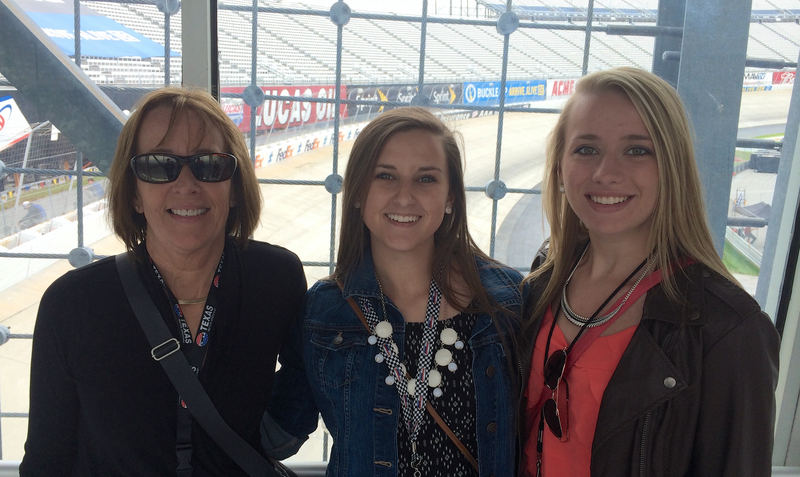 Three women who like cars, at the race track, watching cars.