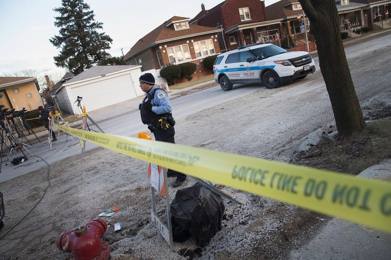 A Chicago police officer guards the perimeter of a crime scene where six people were found slain inside a home on the city's Southwest Side on Feb. 4, 2016. Scott Olson/Getty Images
