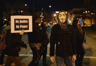 A protester wearing an Anonymous mask looks on as other people demonstrate during a silent protest in the streets of downtown St. Louis on March 14, 2015.  Michael B. Thomas/AFP/Getty Images
