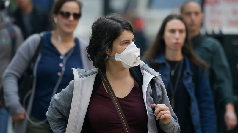 A woman wears a mask in San Francisco Friday. The air quality there is currently unhealthy.