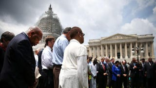 Rep. John Lewis (D-GA) (L) joins members of the US House of Representatives and members of the US Senate in a prayer circle in front of the US Capitol to honor those gunned down inside the historic Emanuel African Methodist Episcopal Church in Charleston South Carolina, June 18, 2015  Mark Wilson/Getty Images