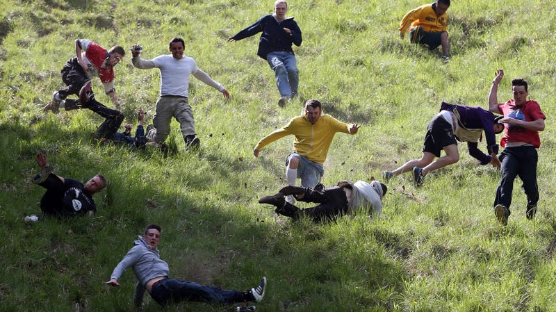 Contestants in the men's race chase a Double Gloucester Cheese down the steep gradient of Cooper's Hill during the annual Bank Holiday tradition of cheese-rolling in 2013.