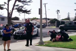 Video footage appears to show officers pinning Cindy Hahn (in pink) to the ground, while one can be seen punching her repeatedly in the head during a 2013 arrest in Carlsbad, Calif.CBS Los Angeles Screenshot