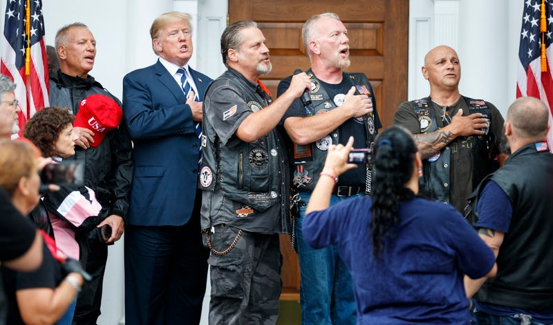 President Donald Trump stands in the rain with members of Bikers for Trump and supporters as they say the Pledge of Allegiance, Saturday, Aug. 11, 2018, at the clubhouse of Trump National Golf Club in Bedminster, N.J.