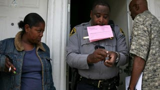 An evicted renter (left) looks on as Alameda County Sheriff Deputy Ken Cammack prepares to post a notice of eviction on the door of an apartment where tenants defaulted on rent payments June 4, 2009, in Oakland, Calif.Justin Sullivan/Getty Images
