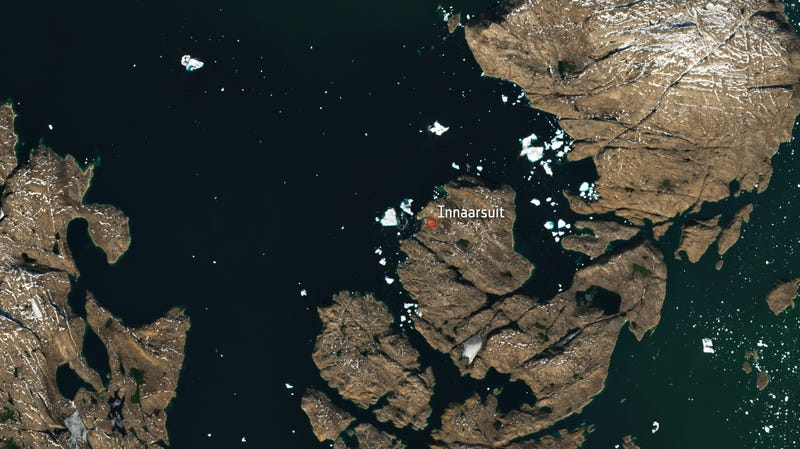 A large iceberg looms over the village of Innaarsuit in this July 9 satellite image.