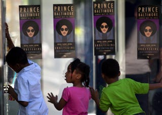 Children look through the glass as fans of musical artist Prince enter his Rally 4 Peace concert in Baltimore May 10, 2015.Andrew Caballero-Reynolds/AFP/Getty Images