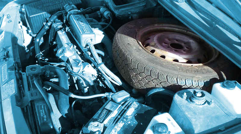 Illustration for article titled How Do You Feel About Spare Tires Jammed In The Engine Bay?