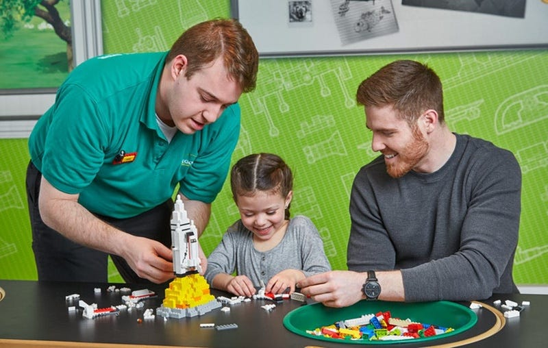 Promotional photo released by Lego showing a Legoland employee helping a child who's accompanied by an adult (Lego)