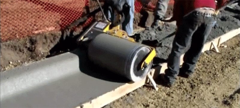 Seeing this curb roller machine shape messy cement into a smooth curb is so satisfying