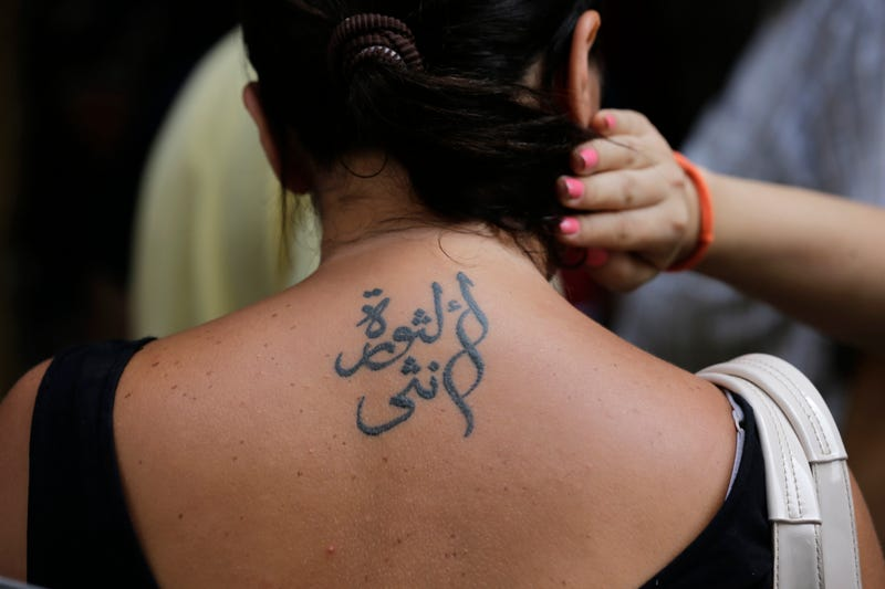 "This tattoo translates to ""Revolution is a woman"" (Image: AP)"