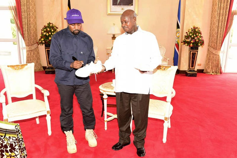 "Kanye West autographs a pair of his sneakers as a gift to Uganda's President Yoweri Museveni, on Oct. 15, 2018, at State House in Entebbe, Uganda. Museveni said he and West held ""fruitful discussions"" about promoting tourism and arts in the East African nation in which the rapper is said to be recording music in a tent."