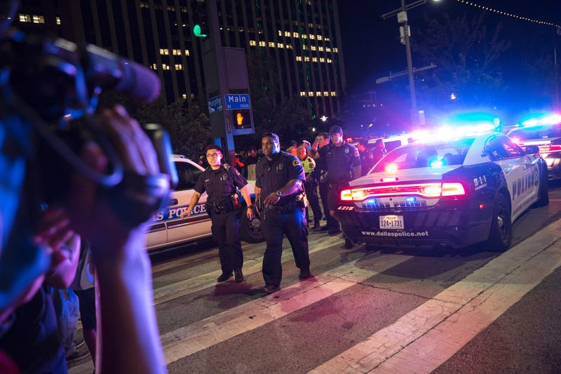 Bystanders stand near police barricades following the sniper shooting in Dallas on July 7, 2016.LAURA BUCKMAN/AFP/Getty Images